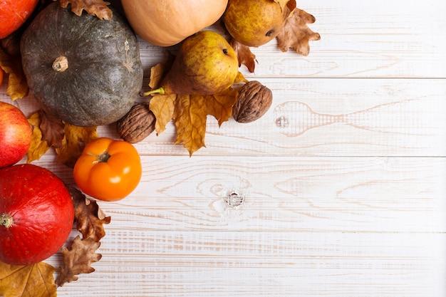 Diverse verdure, zucche, mele, pere, noci, pomodori e foglie secche su un fondo di legno bianco. mood autunnale, copyspace. vendemmia