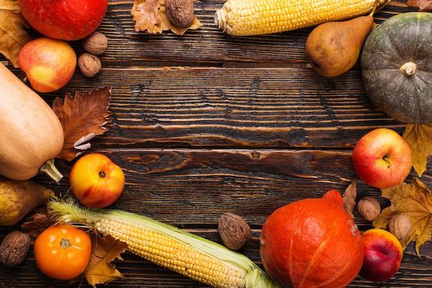 Diverse verdure, zucche, mele, pere, noci, pomodori, mais, foglie gialle secche su fondo in legno. mood autunnale, copyspace. vendemmia