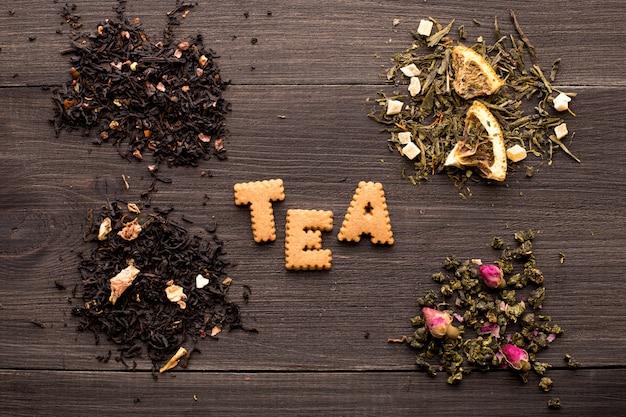Diverse viste di tè e un'iscrizione di biscotto su un tavolo di legno