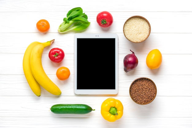 Diversi alimenti naturali - grano saraceno, riso, peperone giallo, pomodori, banane, lattuga, verde, cetriolo, cipolle, tavoletta con schermo nero