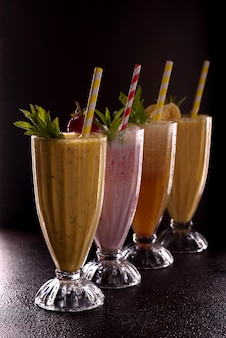 Diversi bicchieri con patatine fritte rinfrescanti fredde con banana, fragola e papaia, con ghiaccio con tubo da cocktail su sfondo nero