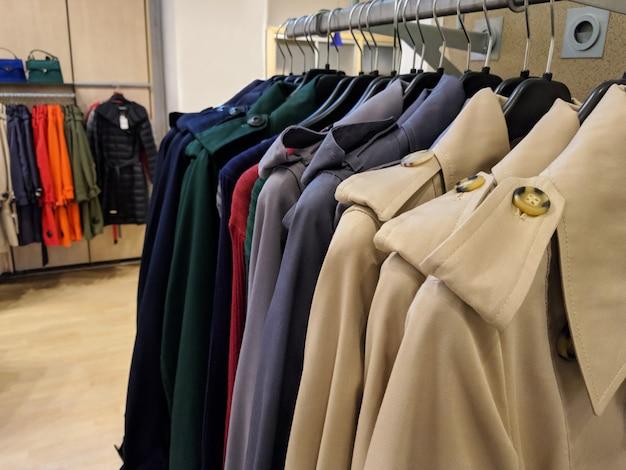 Diversi cappotti autunnali appesi in negozio