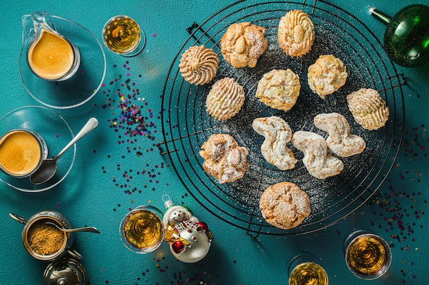Diversi classici biscotti alle mandorle fatti in casa italiani con caffè espresso e bicchieri di liquore dolce sul tavolo, decorazioni di natale di capodanno