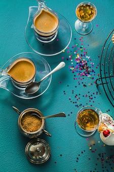 Diversi classici biscotti alle mandorle fatti in casa italiani con caffè espresso e bicchieri di liquore dolce sul tavolo, decorazioni di natale
