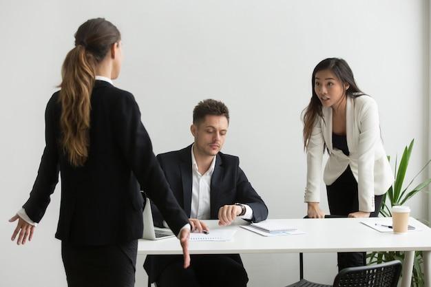 Diversi colleghi che discutono di non puntualità o mancato termine in ufficio