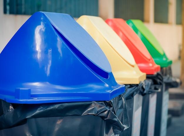 Diversi colorati riciclare bidoni della spazzatura nel parco.