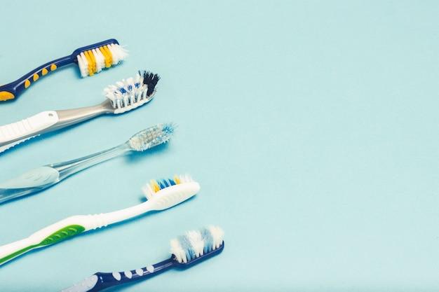 Diversi diversi spazzolini da denti usati su uno sfondo blu. concetto di cambio spazzolino, igiene orale, famiglia grande e amichevole, selezione spazzolino.