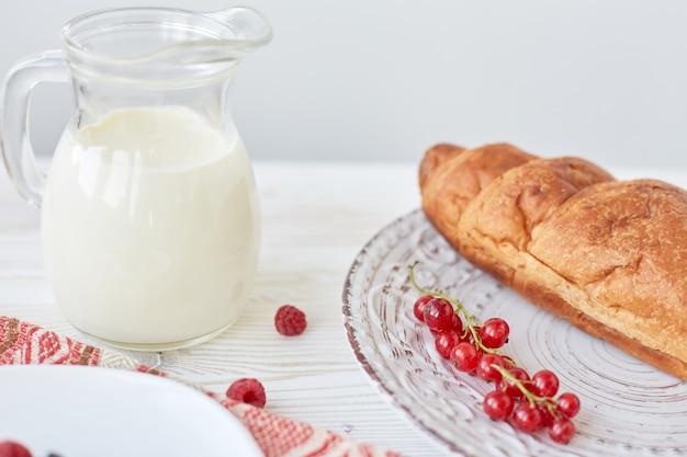 Diversi ingredienti per la colazione. cornetti sul piatto sul bordo di legno, bacche, caffè, latte e miele su una tovaglia bianca. colazione francese tradizionale. vista dall'alto