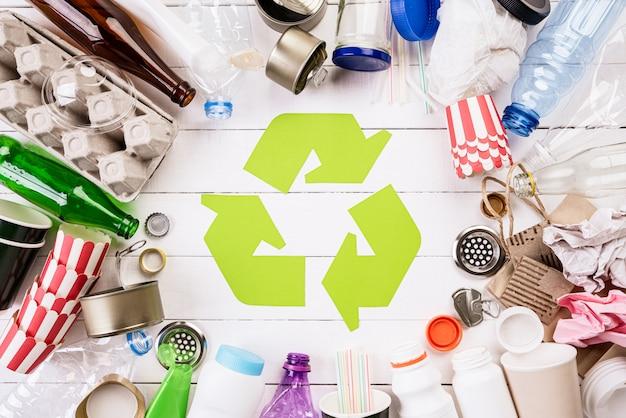 Diversi materiali di immondizia con il simbolo del riciclaggio.