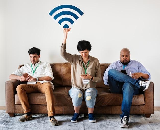 Diversi operai che lavorano al telefono cellulare seduto sul divano