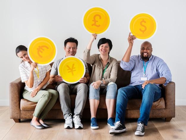 Diversi operai che si siedono e che tengono le icone di valuta