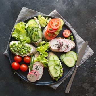 Diversi panini vegani con verdure, ravanello, pomodoro, pane di segale sul nero. antipasto per la festa.