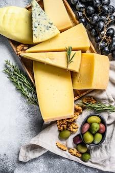 Diversi pezzi di formaggio con olive noci e uva. snack deliziosi assortiti