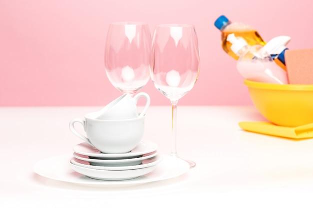 Diversi piatti, una spugna da cucina e una bottiglia di plastica con sapone liquido naturale per lavastoviglie usato per il lavaggio a mano.
