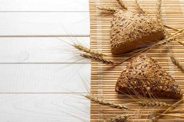 Diversi piccoli cereali a forma di grano triangolare cosparsi di semi di girasole interi