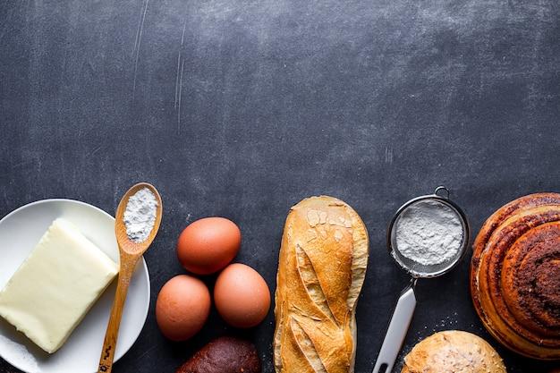 Diversi prodotti da forno freschi e croccanti e ingredienti di cottura su sfondo nero lavagna. copia spazio per ricetta e testo