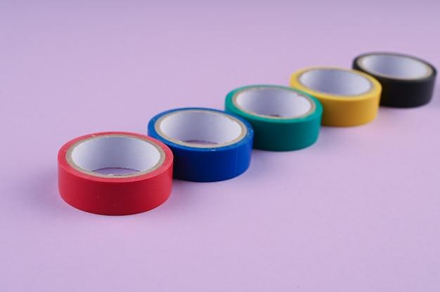 Diversi rotoli rotondi di nastro di plastica colorato si trovano in fila