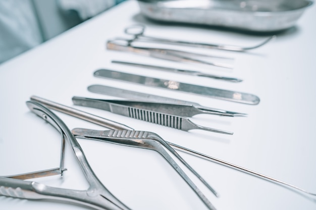 Diversi strumenti chirurgici si trovano su un tavolo bianco