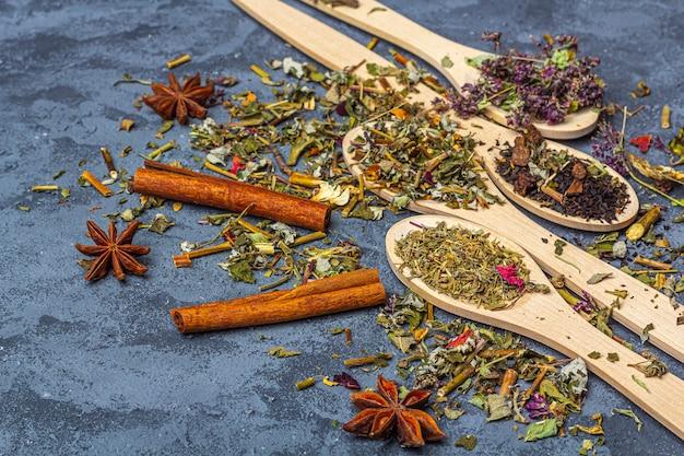 Diversi tè secchi in linea di cucchiai di legno