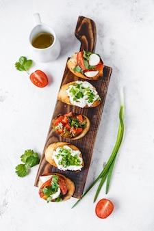 Diversi tipi di bruschette italiane con pomodori, mozzarella ed erbe su una tavola di legno