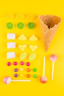 Diversi tipi di caramelle e cono di cialda per gelato sul fondale giallo
