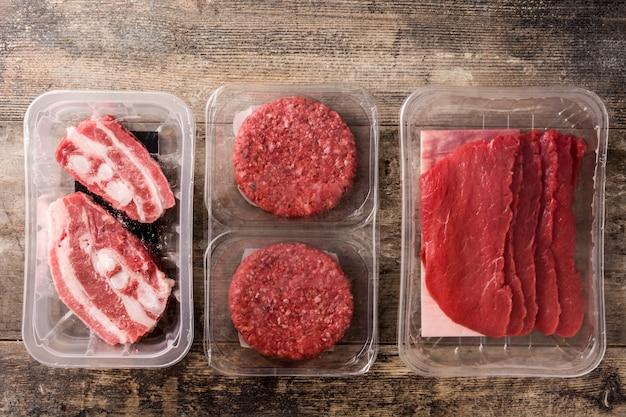 Diversi tipi di carne confezionati in plastica sul tavolo di legno
