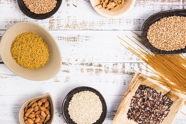 Diversi tipi di cereali integrali in ciotole e spaguetti interi disposti su un tavolo bianco