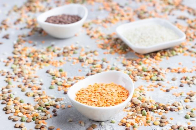 Diversi tipi di chicchi di cereali semole in ciotole di ceramica bianca