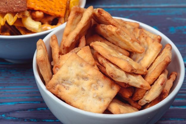 Diversi tipi di cibo spazzatura, bastoncini salati, cracker salati sul tavolo di legno in natura morta