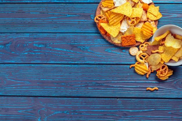 Diversi tipi di cibo spazzatura, bastoncini salati, cracker salati sul tavolo di legno