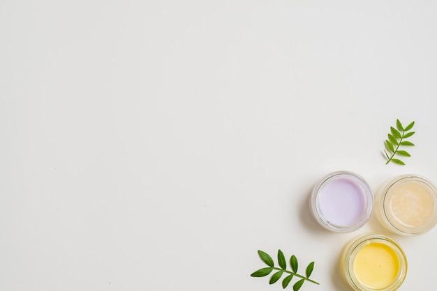 Diversi tipi di crema idratante con foglie su sfondo bianco