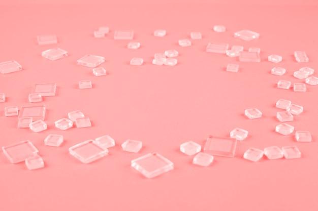Diversi tipi di cubetti di plastica trasparente sparsi su fondo di corallo