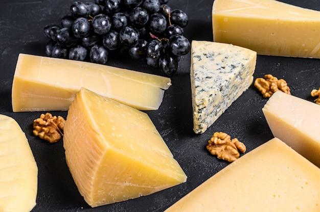 Diversi tipi di deliziosi formaggi con noci e uva. vista dall'alto