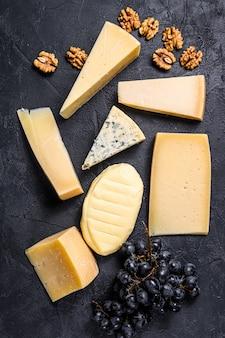 Diversi tipi di deliziosi formaggi con noci e uva.