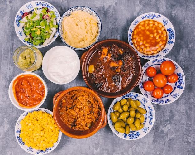 Diversi tipi di deliziosi piatti messicani sul pavimento di cemento