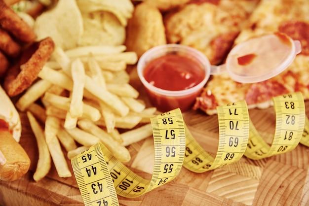 Diversi tipi di fast food e snack sul tavolo con nastro di misurazione