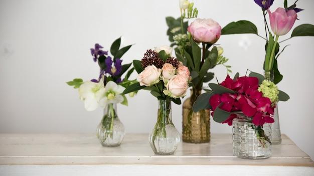 Diversi tipi di fiori nel vaso di vetro sulla scrivania contro il muro bianco