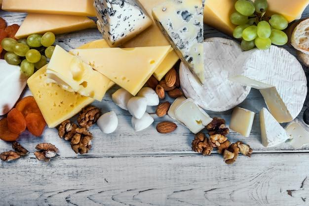 Diversi tipi di formaggi assortiti con frutta, noci, frutta secca