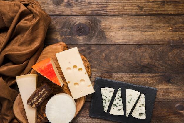 Diversi tipi di formaggi e tessuti di seta marrone sul tavolo