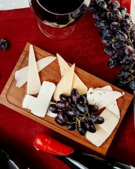 Diversi tipi di formaggi e uva e un bicchiere di vino rosso