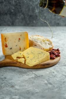 Diversi tipi di formaggi sul tagliere di legno. gorgonzola con ciabatta e pomodori secchi su sfondo grigio. cena con cucina italiana. versare l'olio di semi di girasole sul pane. soft focus, da vicino