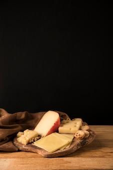 Diversi tipi di formaggio gustoso sul sottobicchiere in legno vicino panno marrone