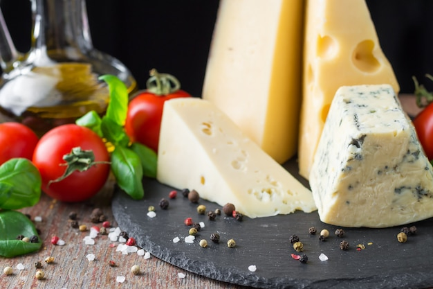 Diversi tipi di formaggio, pomodoro e basilico su un tavolo di legno. cibo vegetariano