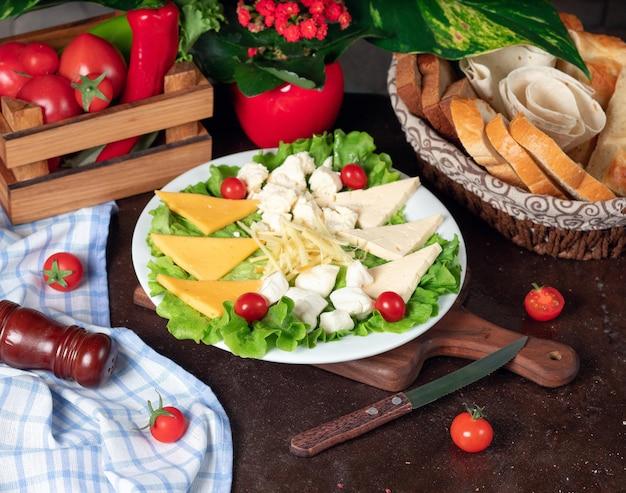 Diversi tipi di formaggio situati su una tavola di legno e decorati con pomodorini, lattuga e pane fresco.