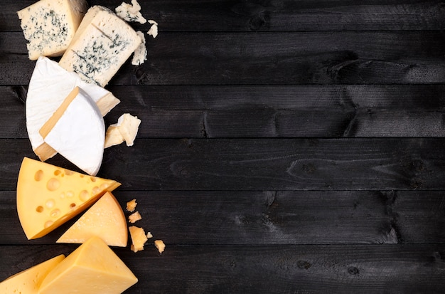 Diversi tipi di formaggio sul tavolo nero. vista dall'alto