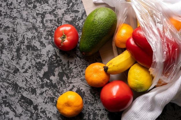 Diversi tipi di frutta e verdura in un sacchetto di plastica, cibo vegetariano e vegano