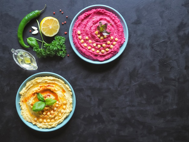Diversi tipi di hummus tradizionale sul tavolo nero. hummus con barbabietola rossa su un tavolo da cucina nero.