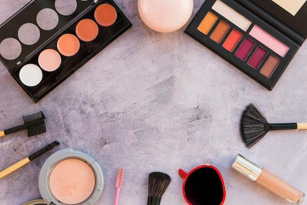 Diversi tipi di palette di trucco colorato con rossetto; polvere compatta; spazzola; mascara; occhiali da sole; su fondo in cemento