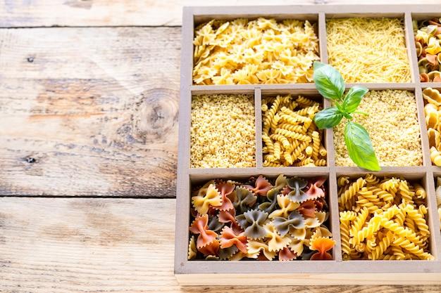 Diversi tipi di pasta cruda italiana in scatola di legno, pasta integrale, pasta, spaghetti, tagliatelle, tagliatelle. vista dall'alto.