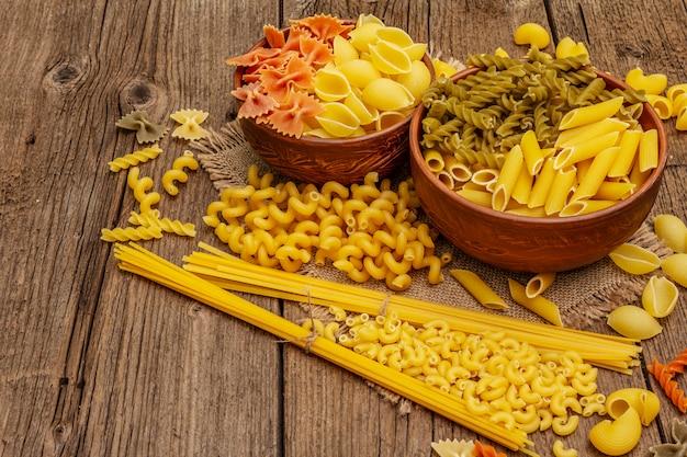 Diversi tipi di pasta in ciotole di ceramica. cibo tradizionale italiano, concetto di alimentazione sana. tavolo in legno rustico